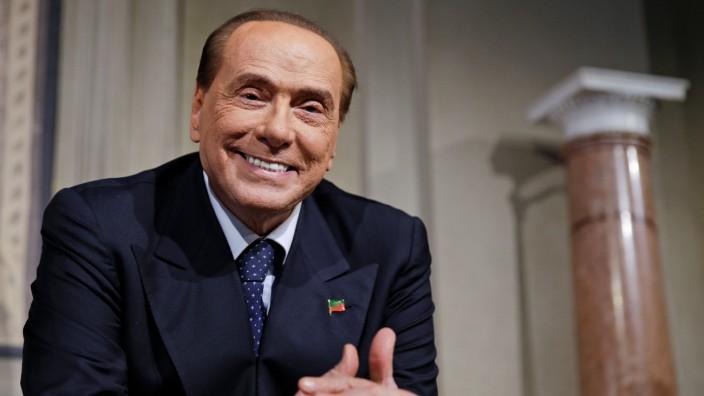 FILE PHOTO: Forza Italia leader Berlusconi smiles as League party leader Salvini (not seen) speaks following a talk with Italian President Sergio Mattarella at the Quirinale palace in Rome
