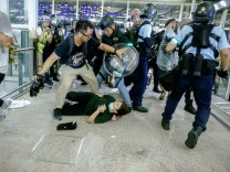 Riot police use pepper spray to disperse anti-extradition bill protesters during a mass demonstration after a woman was shot in the eye, at the Hong Kong international airport, in Hong Kong