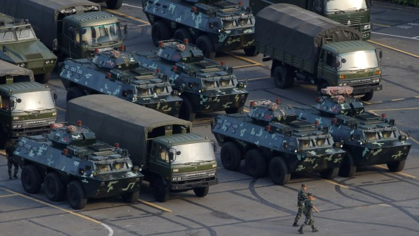 Military vehicles are parked on the grounds of the Shenzhen Bay Sports Center in Shenzhen
