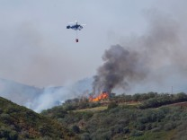 Flames and smoke from a forest fire are seen in the village of Guia.