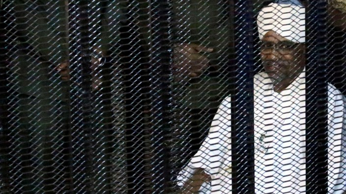 Sudan's former president Omar Hassan al-Bashir sits guarded inside a cage at the courthouse where he is facing corruption charges, in Khartoum