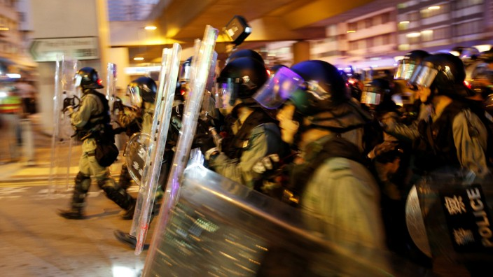 Riot police officers run as they chase demonstrators during clashes at Kowloon Bay in Hong Kong