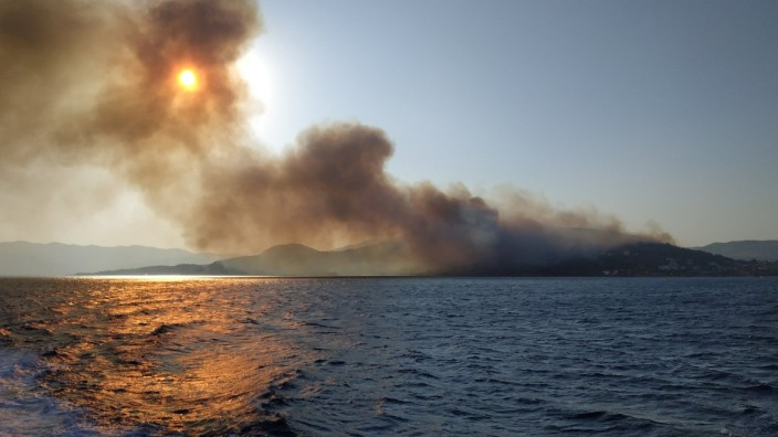 Smoke billows over the sea during a fire on Samos island