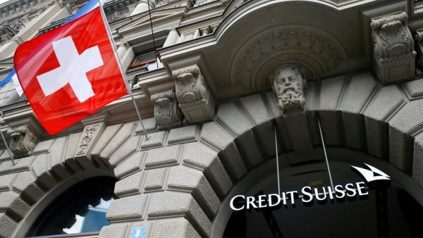 FILE PHOTO: Switzerland's national flag flies below a logo of Swiss bank Credit Suisse in Zurich