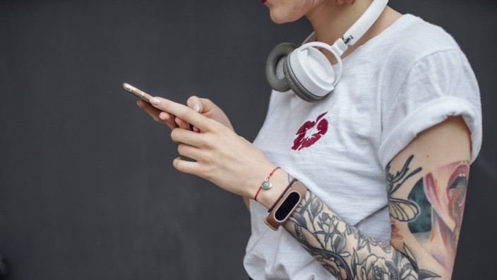Close up of tattooed young woman with headphones using cell phone model released Symbolfoto PUBLICA