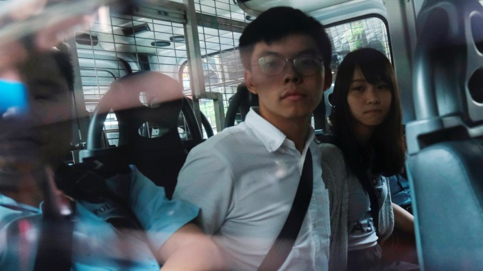 Pro-democracy activists Joshua Wong and Agnes Chow arrive at the Eastern Court by police van after being arrested on suspicion for organising illegal protests, in Hong Kong