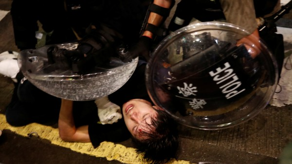 Demonstrator is detained by police officers during a protest in Hong Kong