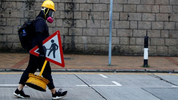 A protestor carries a traffic sign during a protest in Central, Hong Kong