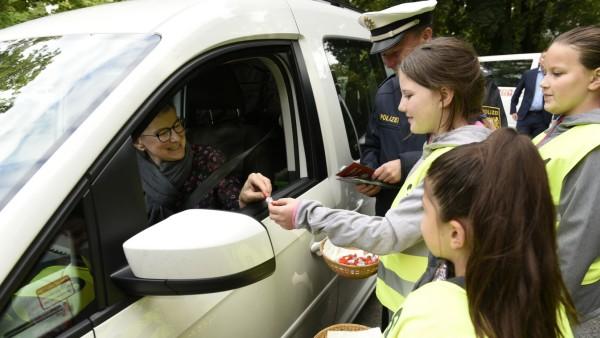 Zum Schulbeginn halten Kinder gemeinsam mit der Polizei Raser auf und überreichen süße Bonbons an Fahrer, die sich vorbildlich verhalten.