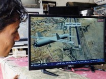 190702 SANAA July 2 2019 Xinhua A man watches TV news on Yemen s Houthi rebels attacking
