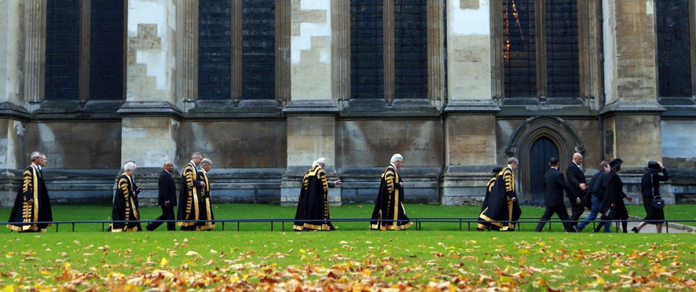 Golden Autumn leaves are on the ground as Supreme Court Judges looking resplendent in their black ro