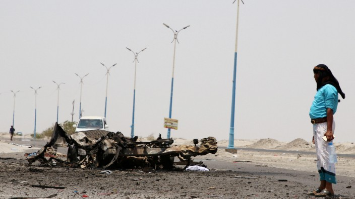 A man stands past the wreckage of government forces vehicles destroyed by UAE air strikes near Aden