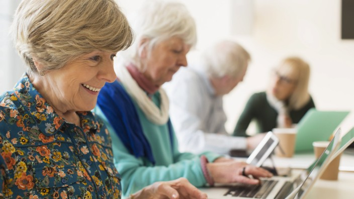 Senior women using laptops in conference room meeting Senior women using laptops in conference room
