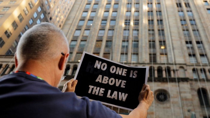 FILE PHOTO: Demonstrators hold protest signs as part of a demonstration in support of impeachment hearings in New York