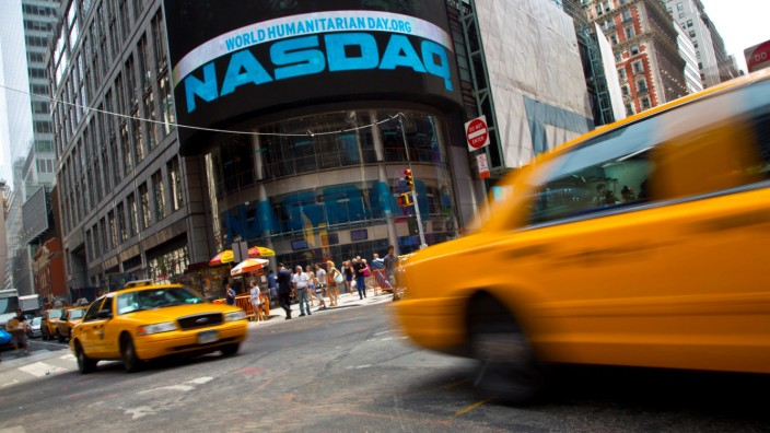 FILE PHOTO: Taxi cabs drive  past the Nasdaq MarketSite in New York's Times Square