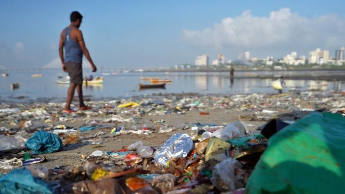 A man walks on a garbage-strewn beach in Mumbai