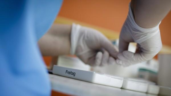 Eine Pflegerin sortiert Medikamente in Tablettendispenser in einem Pflegeheim, 27.04.2018, Berlin. NUR ZUR REDAKTIONELL