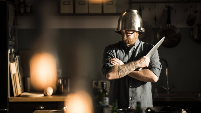 Man with kitchen knife standing in kitchen wearing colander as helmet model released Symbolfoto pro