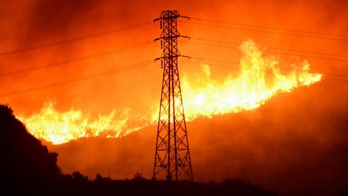 Firefighters battle a wind-driven wildfire in Sylmar, California