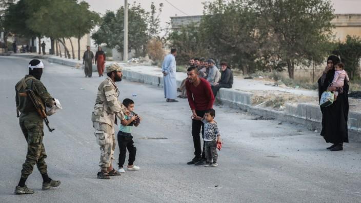 Syrien-Krieg: Soldaten der türkisch unterstützten syrischen Nationalarmee sprechen mit Anwohnern