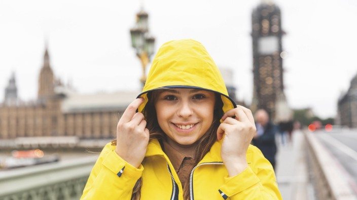 Portrait of smiling young woman wearing yellow raincoat on a rainy day London UK model released Sy