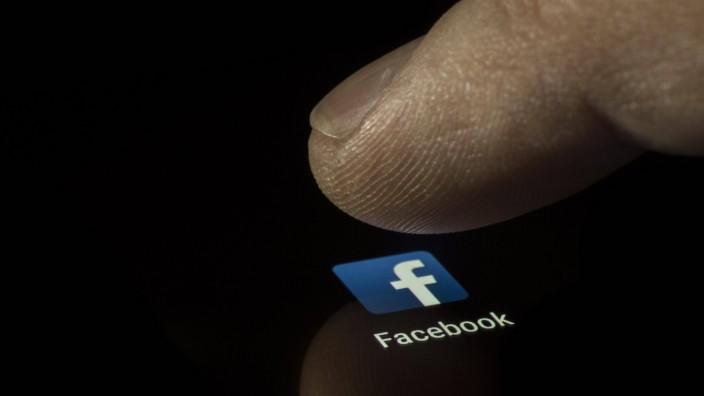 Facebook App Icon auf einem Display mit Finger Soziales Netzwerk Social Media Handy Smartphone