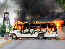 A burning bus, set alight by cartel gunmen to block a road, is pictured during clashes with federal forces following the detention of Ovidio Guzman, son of drug kingpin Joaquin 'El Chapo' Guzman, in Culiacan