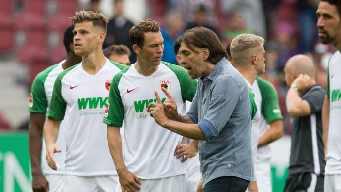 l-r: Stephan Lichtsteiner 2 (FC Augsburg) bekommt von Chef-Trainer Martin Schmidt (FC Augsburg) nach Spielende einige e