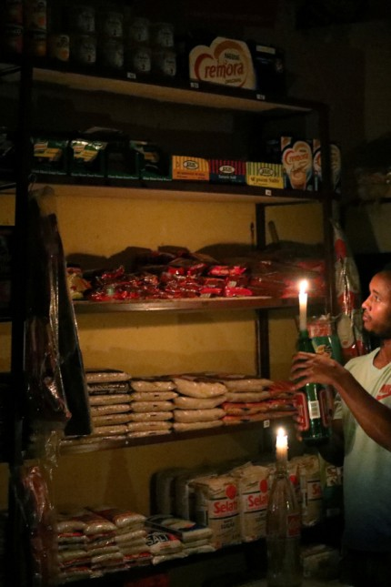 FILE PHOTO: Mulugeta Desalegn, an owner of a convenience store, or 'spaza shop', picks an item for a customer as he holds a candle, in Senaone