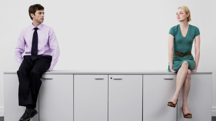 Young male and female business people sitting on office cabinets,model released, Symbolfoto,property released PUBLICATIO