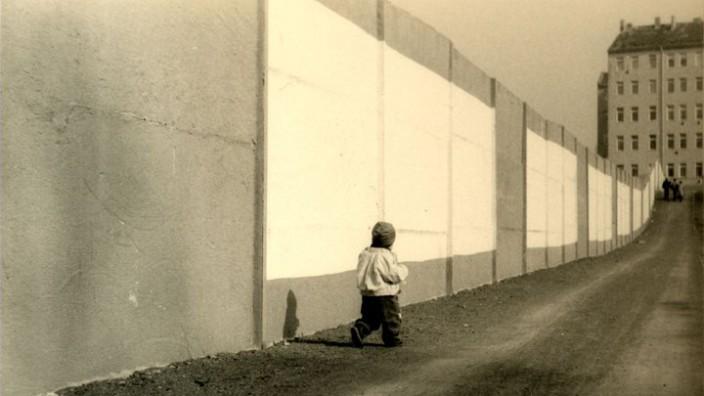 Die Tochter von Anja Maier an der Berliner Mauer.
