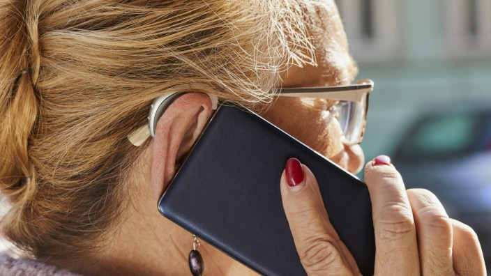 Close up of senior woman with hearing aid using smartphone model released Symbolfoto property releas