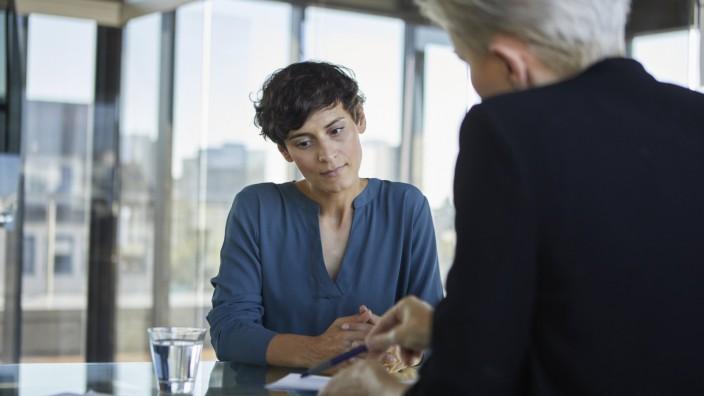 Two businesswomen talking at desk in office model released Symbolfoto property released PUBLICATION