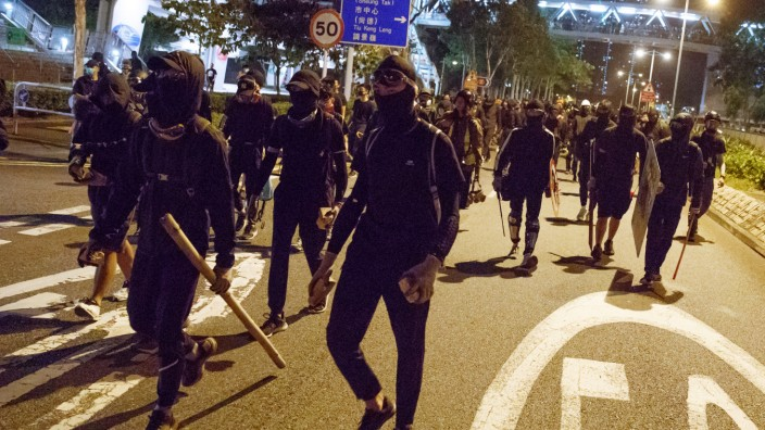 Protesters walk a street to clash with police in Tseung Kwan O in Hong Kong