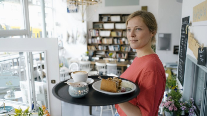 Young woman serving coffee and cake in a cafe model released Symbolfoto property released PUBLICATIO