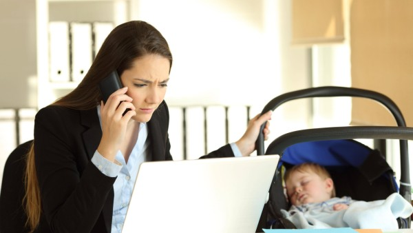 Stressed mother working taking care of her baby at office model released Symbolfoto PUBLICATIONxI