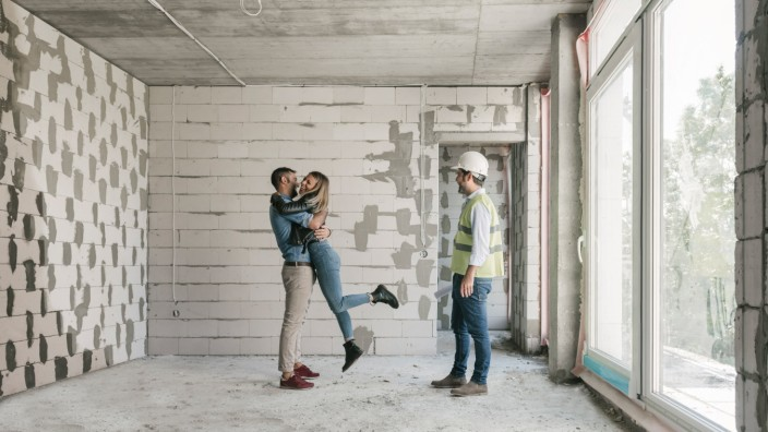 Architect having a meeting with happy future owners on construction site model released Symbolfoto property released PUB