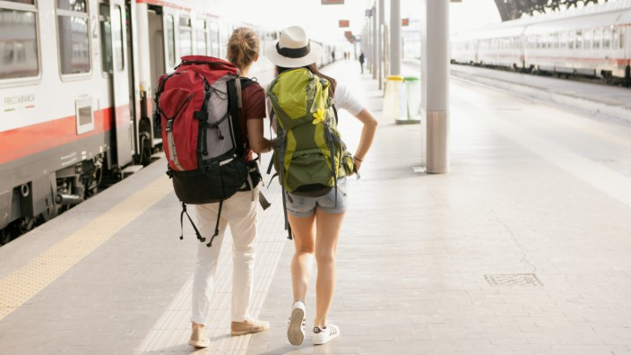 Zwei Reisende mit Rucksack am Bahnhof von Mailand