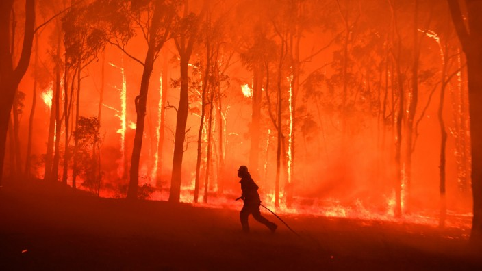 NSW Fire and Rescue officer protects the Colo Heights Public School from being impacted by the Gospers Mountain fire near Colo Heights south west of Sydney