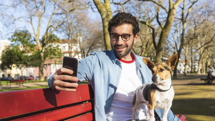 Portrait of young man sitting with his dog on park bench taking selfie with smartphone model release