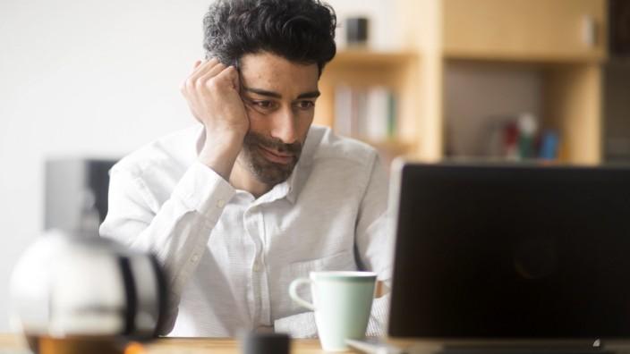 Portrait of businessman at desk looking at laptop model released Symbolfoto property released PUBLICATIONxINxGERxSUIxAU