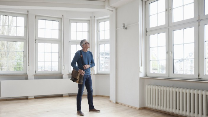 Man looking around in empty apartment model released Symbolfoto property released PUBLICATIONxINxGER