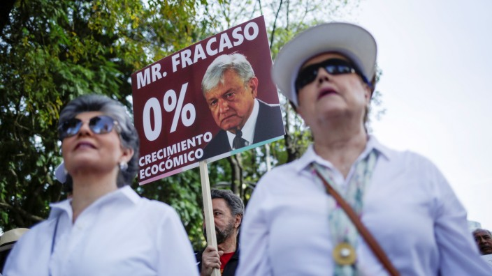 A demonstrator holds up a sign during a march to protest against violence on the first anniversary of President Andres Manuel Lopez Obrador taking office, in Mexico City