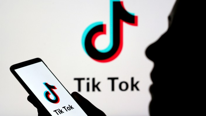 FILE PHOTO: Person holds a smartphone with Tik Tok logo displayed in this picture illustration