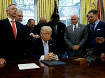 FILE PHOTO: Faith leaders place their hands on the shoulders of U.S. President Trump as he takes part in a prayer for those affected by Hurricane Harvey in the Oval Office of the White House in Washington