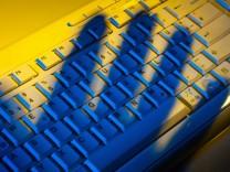 Computertastatur und Schatten einer Hand. Diebstahl von Daten. McPBBO McPBBO