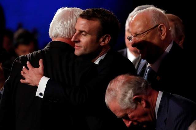 German President Frank-Walter Steinmeier and French President Emmanuel Macron hug at the World Holocaust Forum marking 75 years since the liberation of the Nazi extermination camp Auschwitz, at Yad Vashem Holocaust memorial centre in Jerusalem