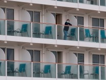 A passenger wearing face mask looks out from a cabin on the World Dream cruise ship, after it had been denied entry in Taiwan amid concerns of coronavirus infection on board, at the Kai Tak Cruise Terminal in Hong Kong