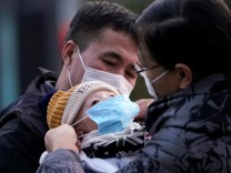 Passengers help a baby wear a mask at the Shanghai railway station