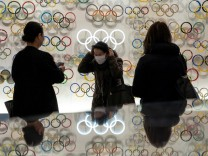 People wearing protective face masks, following an outbreak of the coronavirus, are seen at The Japan Olympics museum in Tokyo